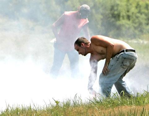 Members of a road maintenance crew try to control a grass fire near Lincoln, Neb., using their shirts and boots, July 17, 2007. Dry conditions and 99 degree temperatures contributed to the fire. (AP)