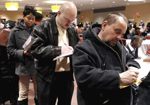 Detroit residents fill out applications while attending a job fair, Feb. 2010. (AP)