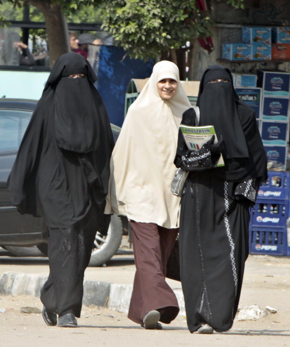 """Students wearing the niqab walk with another wearing the """"Khemar"""" in Cairo, Egypt. (AP)"""