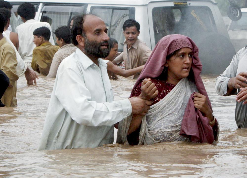 Pakistani villagers evacuate a flooded village near Nowshera,  Pakistan.(AP)