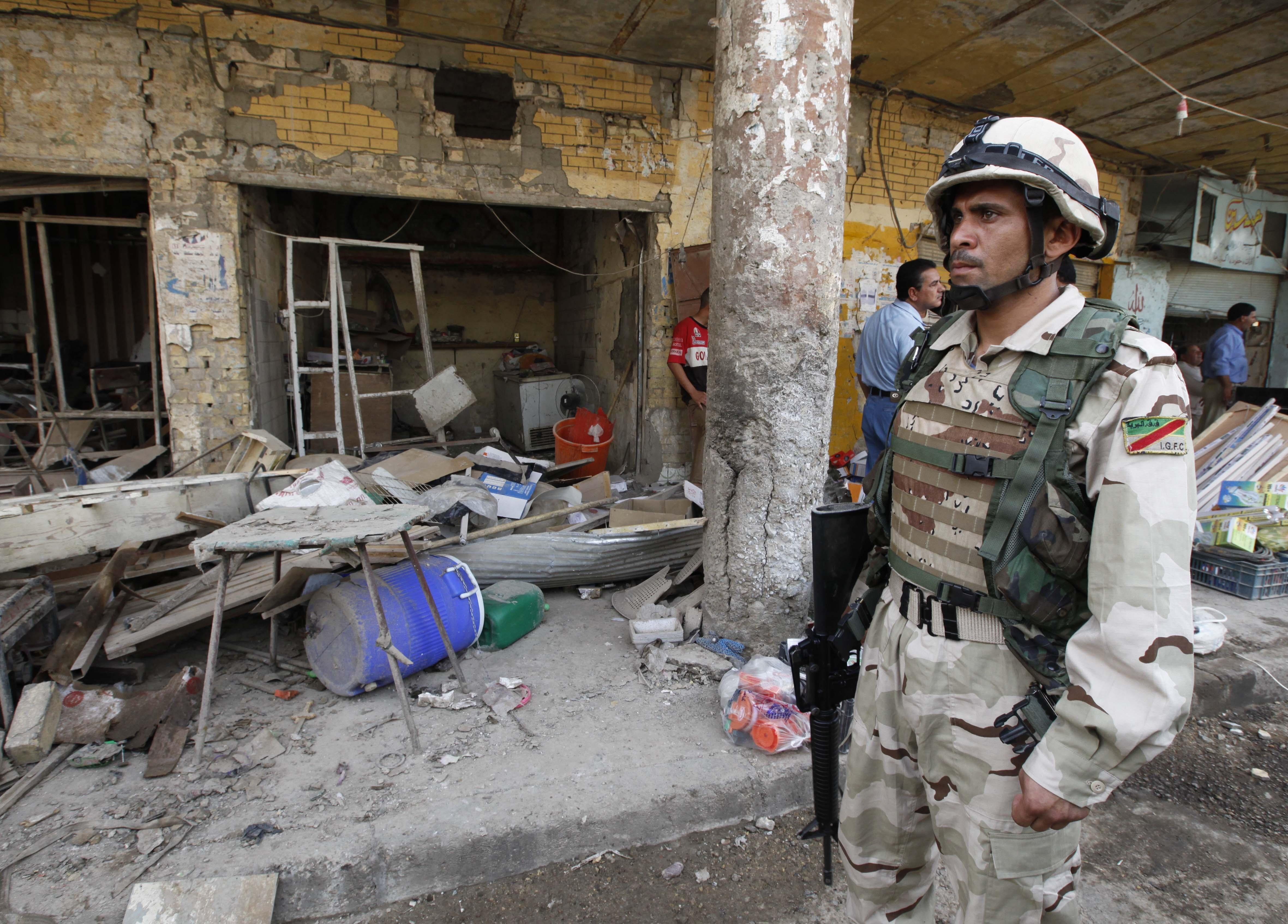 An Iraqi solider stands guard at the scene of a car bomb attack in Kut, southeast of Baghdad. A car bomb ripped through an outdoor market in a mainly Shiite city southeast of Baghdad in the deadliest of a series of attacks that killed and injured scores on Tuesday, officials said. (AP)