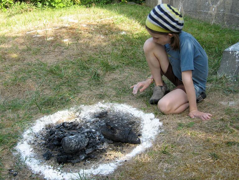 Visitor Lydia McCarthy tries her hand at island art. (Andrea Shea/WBUR)