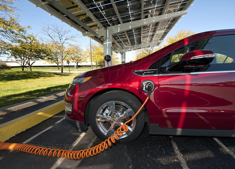 The electric Chevy Volt at a charging station. (Courtesy of GM)