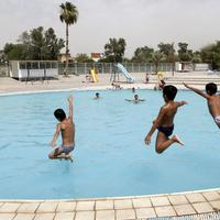 Boys leap into a public swimming pool in Baghdad in June. (AP)