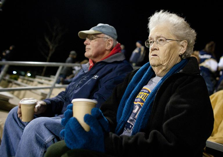 Bill and Frances Theis keep warm with hot cocoa and wait for their grandson to take the field after halftime at a Shrewsbury Senior High School football game. (Dominick Reuter for WBUR)