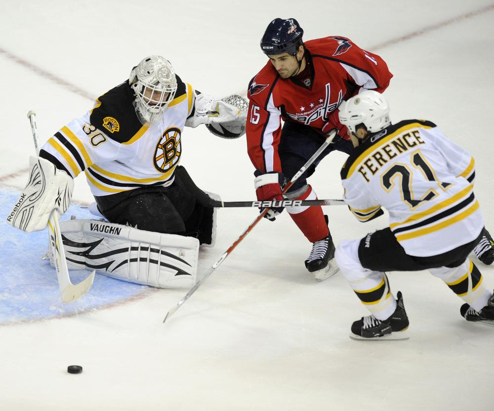 Capitals right wing Boyd Gordon (15) battles for the puck against Bruins goalie Tim Thomas, left, and defenseman Andrew Ference, right, during the first period , Friday, in Washington. (AP Photo/Nick Wass)