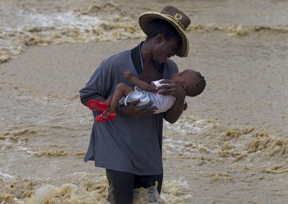A man carries a child while wading across a flooded street during the passing of Hurricane Tomas in Leogane, Haiti, Friday. (AP Photo/Ramon Espinosa)