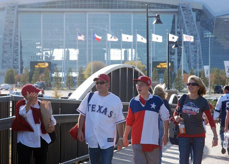 Rangers fans walk to the baseball stadium with Cowboys Stadium in their wake. (Karen Given/WBUR)