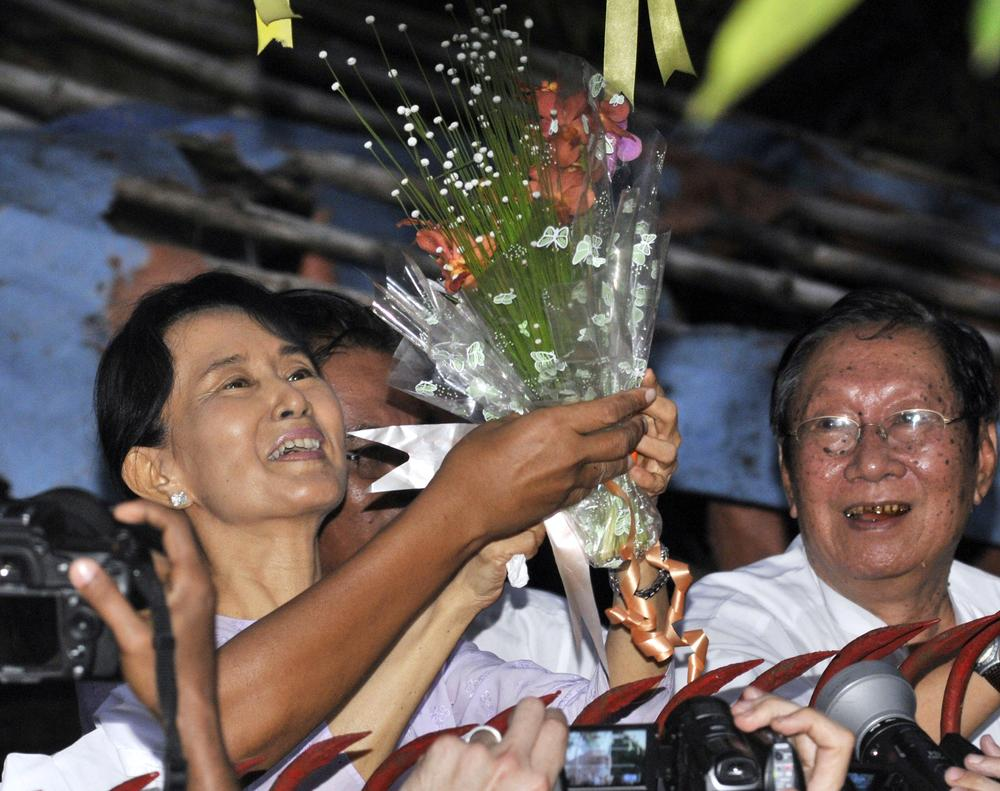 Myanmar's pro-democracy leader Aung San Suu Kyi, left, smiles after she received flowers from her supporters as she stands at the gate of her home Saturday. (AP)