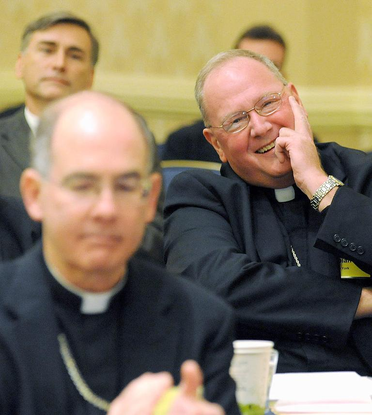 Archbishop Timothy Dolan, right, of New York, reacts after being elected president of the U.S. Conference of Catholic Bishops on Tuesday in Baltimore. (AP)