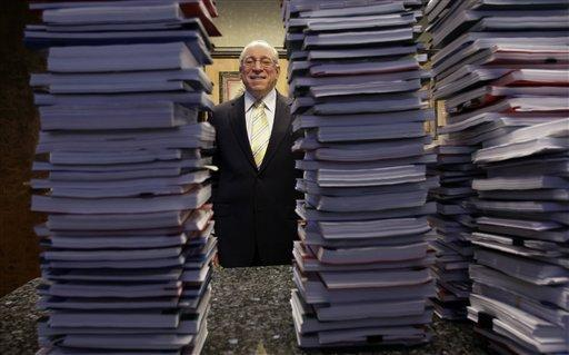 Lawyer Peter Ticktin, of The Ticktin Law Group poses behind stacks of depositions from 150 robosigners, alleging that the court documents reveal an industry-wide banking scheme to defraud homeowners, in Deerfield Beach, Fla. (AP)