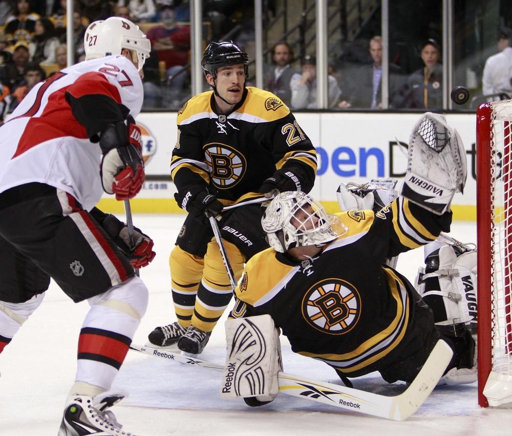 Bruins'  Tim Thomas, right, reaches for the puck as  Andrew Ference (21) and Ottawa Senators' Alex Kovalev (27), of Russia, look on in the third period, Saturday, in Boston.  (AP Photo/ Michael Dwyer)