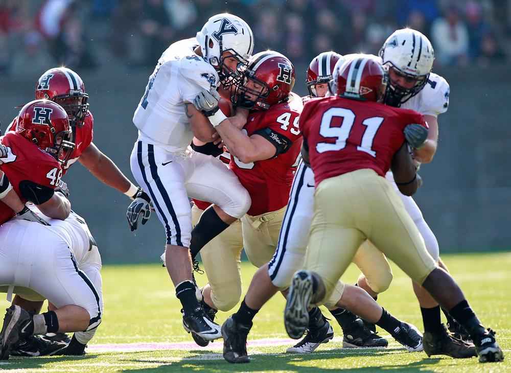Yale Bulldogs running back Alex Thomas is stopped by Harvard Crimson line backer Alex Gedeon during the first half of The Game on Saturday. (Greg M. Cooper/AP)