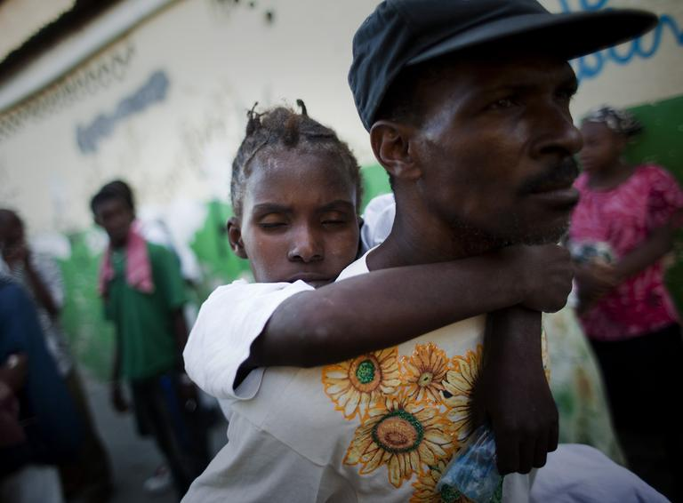 A young woman suffering cholera symptoms is carried by a relative to St. Catherine hospital, run by Doctors Without Borders, in the Cite Soleil slum in Port-au-Prince, Haiti, Friday Nov. 19, 2010. (AP)
