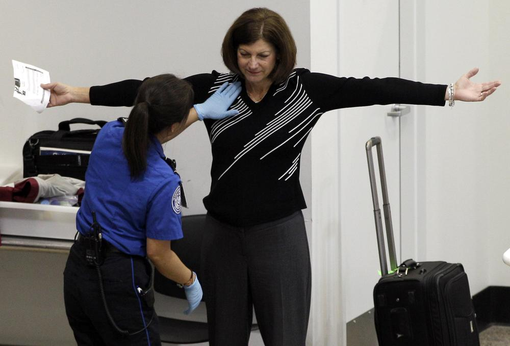 A woman undergoes a pat-down during TSA security screening, Friday, at Seattle-Tacoma International Airport in Seattle. (AP Photo/Ted S. Warren)