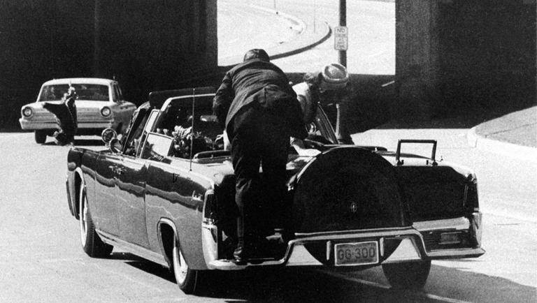 Secret Service agent Clint Hill jumps on the back of the Kennedy motorcade after President John F. Kennedy was shot in Dallas on Nov. 22, 1963. (AP)