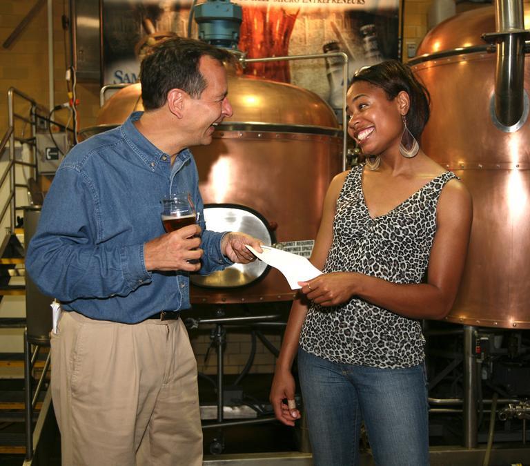 Jim Koch, left, handing Carlene O'Garro of Delectable Desires a check as part of a micro-lending program. (Courtesy Boston Beer Company)