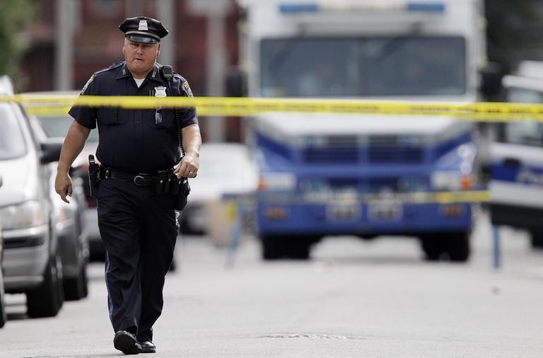 A police officer walks near the scene of the Mattapan shootings on Sept. 29. (AP)