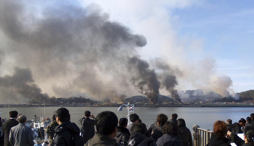 South Korean villagers watch smoke rising from South Korea's Yeonpyeong island near the border against North Korea. (AP)