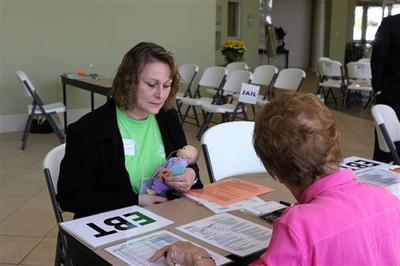 Volunteer Evelyn Williams calculates the groceries she can offer school principal Jinjer Taylor,  who is cast in the role of  an impoverished mother using food stamps in a poverty simulation in Gainesville, Ga. (AP)