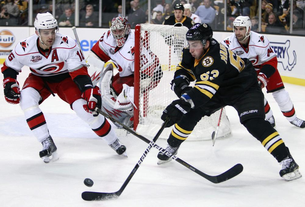 Bruins' Brad Marchand (63) tries to gain  control of the puck as Carolina Hurricanes' Brandon Sutter, left, defends in the second period , Friday, in Boston. (AP Photo/Michael Dwyer)
