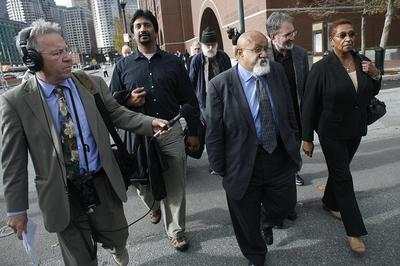 Boston City Councilor Chuck Turner, center, leaves the Moakley Courthouse Oct. 29 after being found guilty on all counts in a corruption trial. (Dominick Reuter for WBUR)