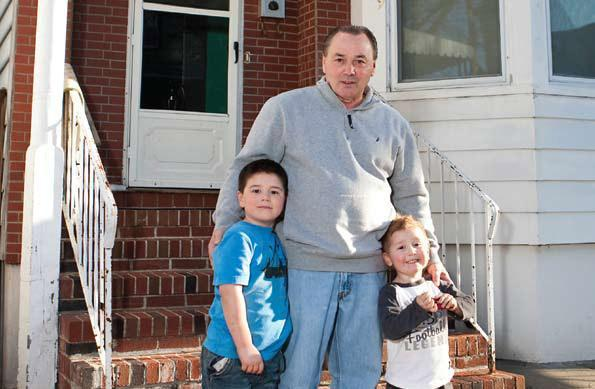 Buddy Wilson with his grandsons outside the East Boston home Boston Community Capital helped him afford. (Courtesy photo)