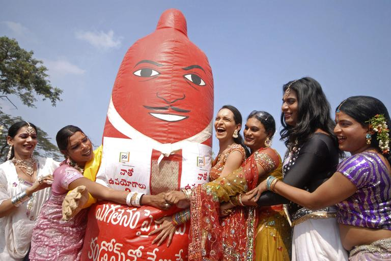 Indian transgenders stand with a giant condom during an awareness rally in Hyderabad, India, Wednesday.