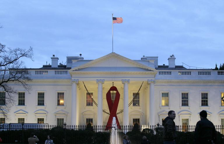 A red ribbon hangs from the the North Portico of the White House in Washington, Tuesday, to commemorate World AIDS Day.