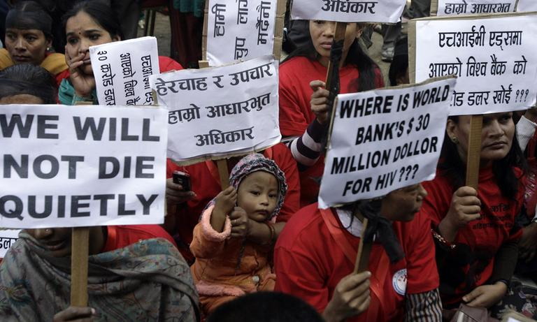Nepalese HIV-positive people and activists hold placards demanding access to adequate medical services during a rally to in Katmandu, Nepal, Wednesday.