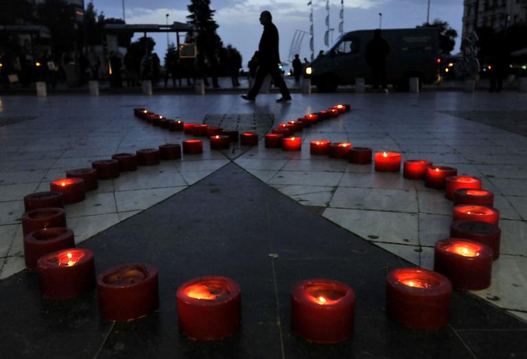 A man walks behind candles form a ribbon touring event at the city of Thessaloniki, northern Greece, Wednesday.