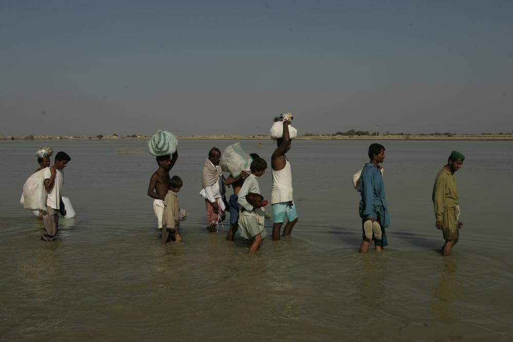 Survivors in Pakistan wade through water in their village of Khairpur Nathan Shah, which is still surrounded by flood waters, months after floods hit the country, claiming 2,000 lives and affecting 20 million people. (AP)