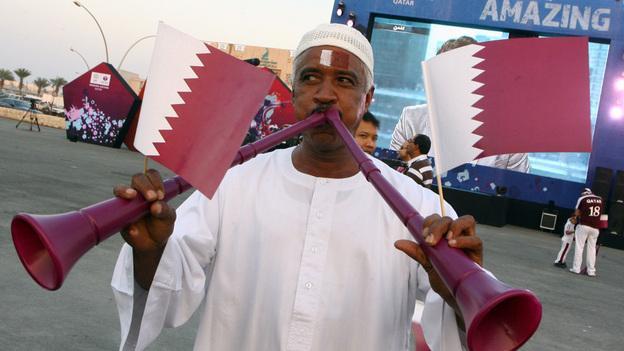 A Qatari man waves the national flag as he blows vuvuzelas at Doha's traditional souk. FIFA announced Thursday that Qatar won its bid to host the 2022 World Cup. (AP)