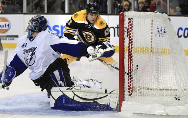 Boston left wing Mllan Lucic, rear, shoots the puck past Tampa Bay goalie Mike Smith during the second period of the game in Boston on Thursday.(AP)