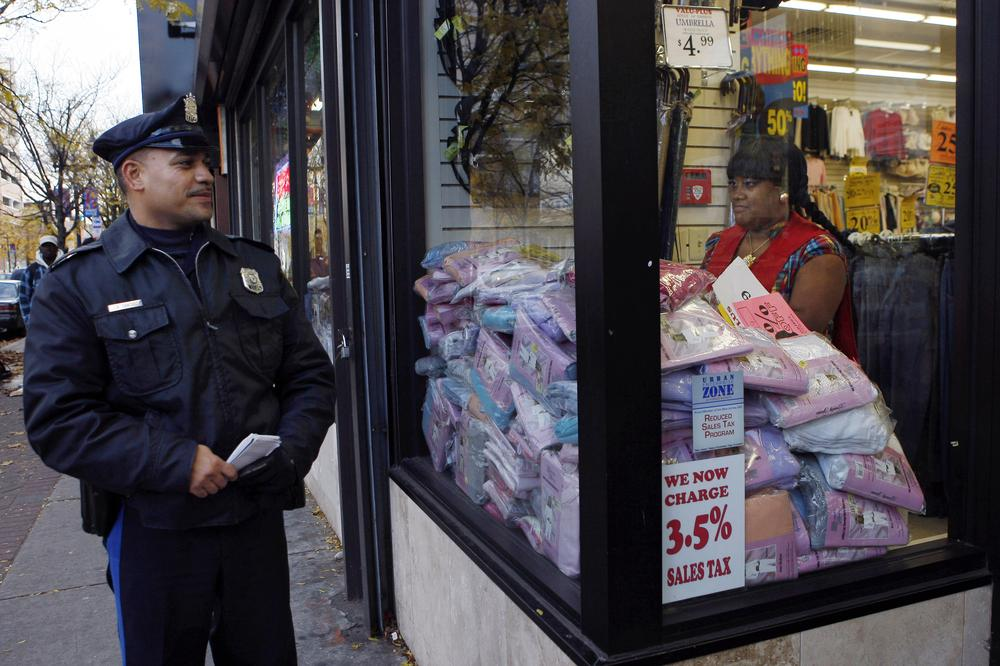 Camden Police Officer L.A. Sanchez walks a beat in a downtown shopping area in Camden, N.J.  Camden's city council last night voted to slash the police force in half and the fire department by one-third, as it struggles to meet a $26 million shortfall. (AP)