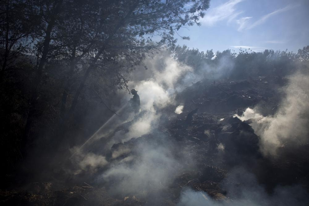An Israeli firefighter attempts to extinguish a blaze in the youth village (boarding school) of Yemin Orde, near the northern city of Haifa, Israel, Sunday. (AP)