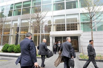 People enter the Goldman Sachs headquarters in New York. According to the New York Times, Goldman plans bonuses early and often sets the standard for other banks. (AP)