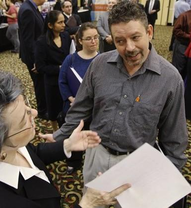 Brad Steele, right, interviews with Betsy Harris, left, of Express Employment Professionals at a National CareerFair, in Cincinnati, Ohio. (AP)