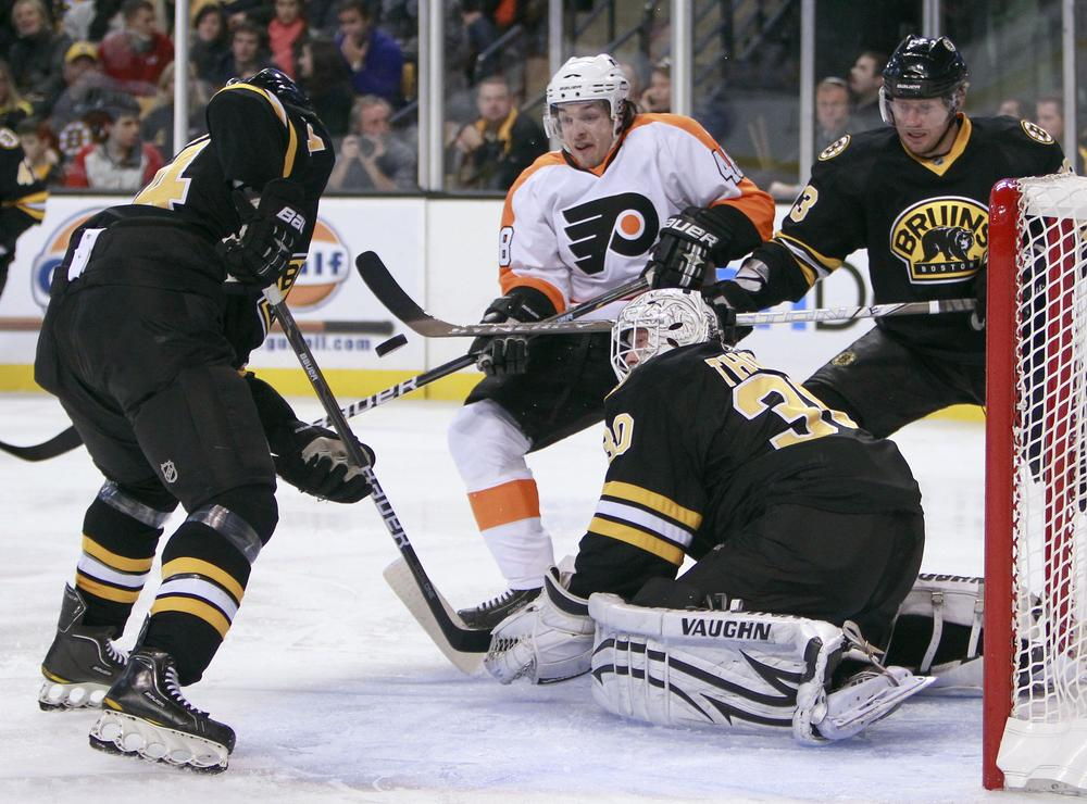 Philadelphia Flyers' Danny Briere, (48) looks for the rebound as Boston Bruins' Dennis Seidenberg, left,  moves to clear the puck from in front of Bruins goalie Tim Thomas (30) in the third period, Saturday, in Boston. (AP)
