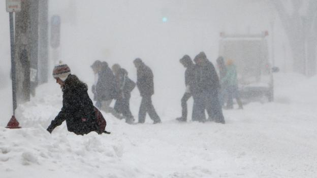 Pedestrians make their way to a Minnesota college basketball game against Eastern Kentucky on the University of Minnesota campus during a snowstorm in Minneapolis, Saturday.