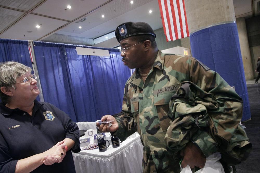 James Johnson, a 22-year Army veteran, talks with Pat Cooke, left, a recruiter for the Clearwater, Fla. police department, at a veterans job fair in New York. (AP)