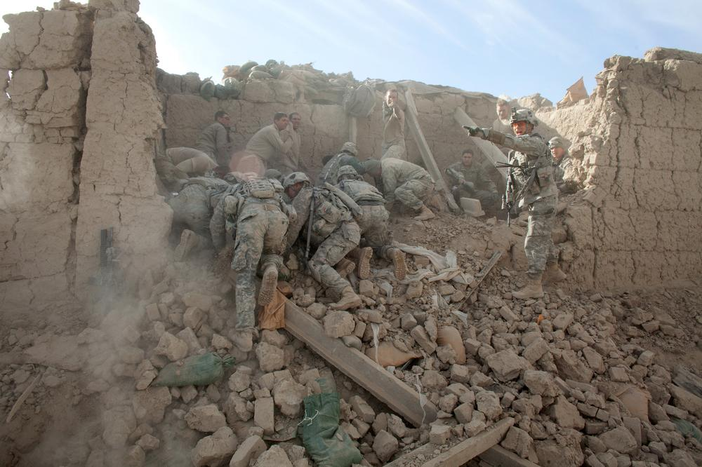 Soldiers dug through the rubble after a fatal bomb destroyed an outpost in Kandahar Province.  (Tyler Hicks/The New York Times)
