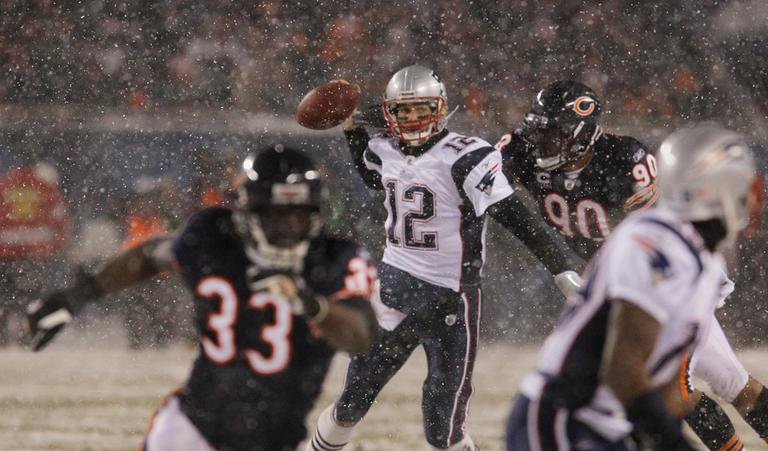 New England Patriots quarterback Tom Brady, center, is sacked by Chicago Bears defensive end Julius Peppers in the second half of an NFL football game in Chicago, Sunday. (AP)