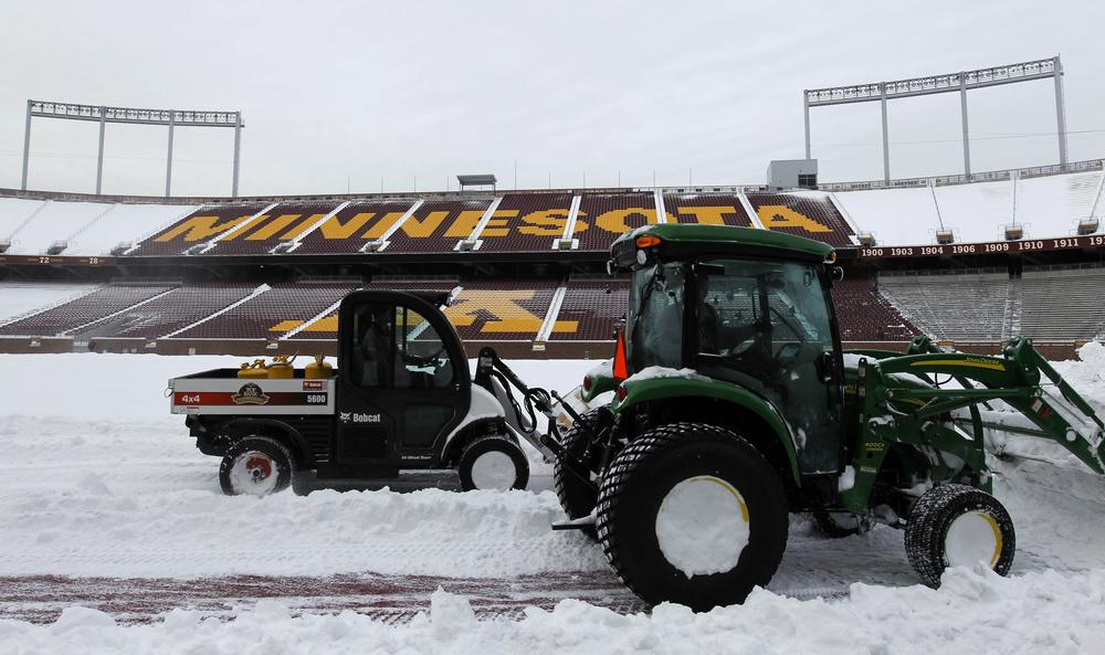 Workers clear snow from TCF Bank Stadium at the University of Minnesota in Minneapolis. (AP)