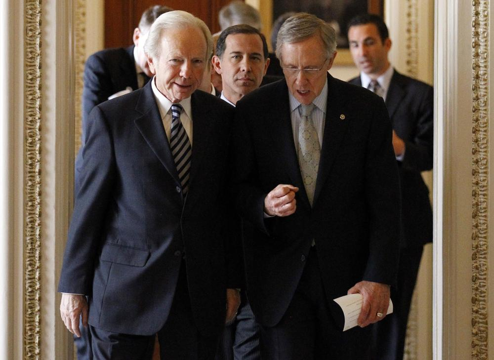 "Sen. Joe Lieberman, I-Conn., left, and Senate Majority Leader Sen. Harry Reid, D-Nev., right, with Joe Solmonese, president of the Human Rights Campaign, center, head to a news conference about the military's ""Don't Ask Don't Tell"" policy. (AP)"