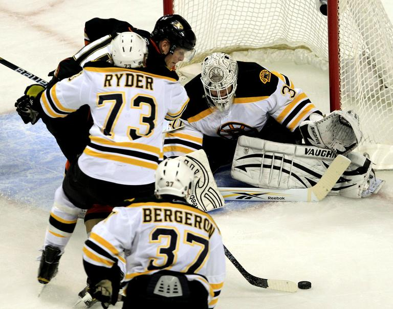 Boston goalie Tim Thomas, left, drops his stick to the ice as Anaheim right wing Corey Perry shoots during the second period of the game in Boston on Monda. Clearing Perry from the crease is Bruins right wing Michael Ryder. (AP)