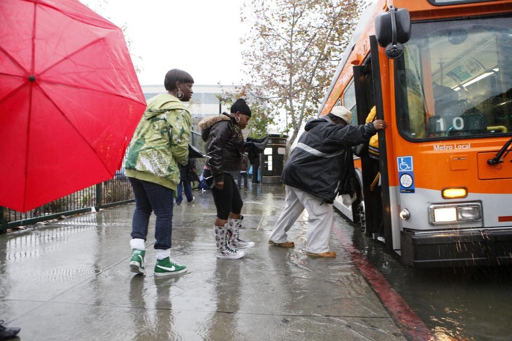 Pedestrians walk through rising water as they catch a city  bus in  Los Angeles. (AP)