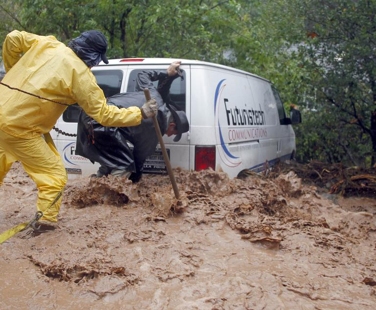 Residents wade through in flood waters to secure a van and prevent it from going into a river in Silverado Canyon, Calif., Wednesday. (AP)