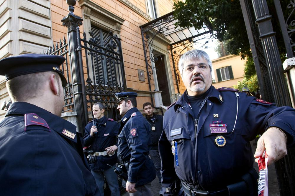 Police officers stand outside the Chilean embassy, in Rome, after a pair of package bombs exploded at the Swiss and Chilean embassies in the city. (AP)