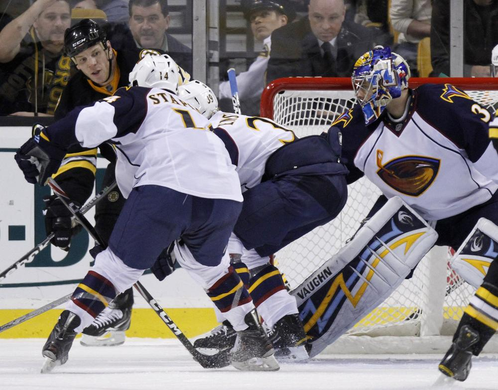 Boston's Shawn Thornton, behind left, tries to get the puck into the net past Atlanta's Tim Stapleton (14), Tobias Enstrom, center, of Sweden, and goalie Ondrej Pavelec, right, of the Czech Republic, in the third period of the game on Thursday in Boston. The Bruins won 4-1. (AP)